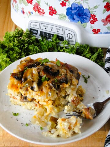 Slice of crock pot breakfast casserole on white plate with fork in front of crock pot.