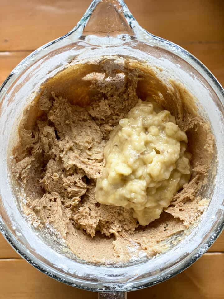Wet and dry ingredients combined with mashed bananas on top.