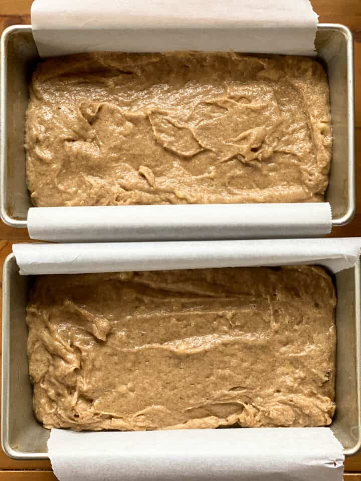 Bread batter in parchment lined rectangle loaf pans.