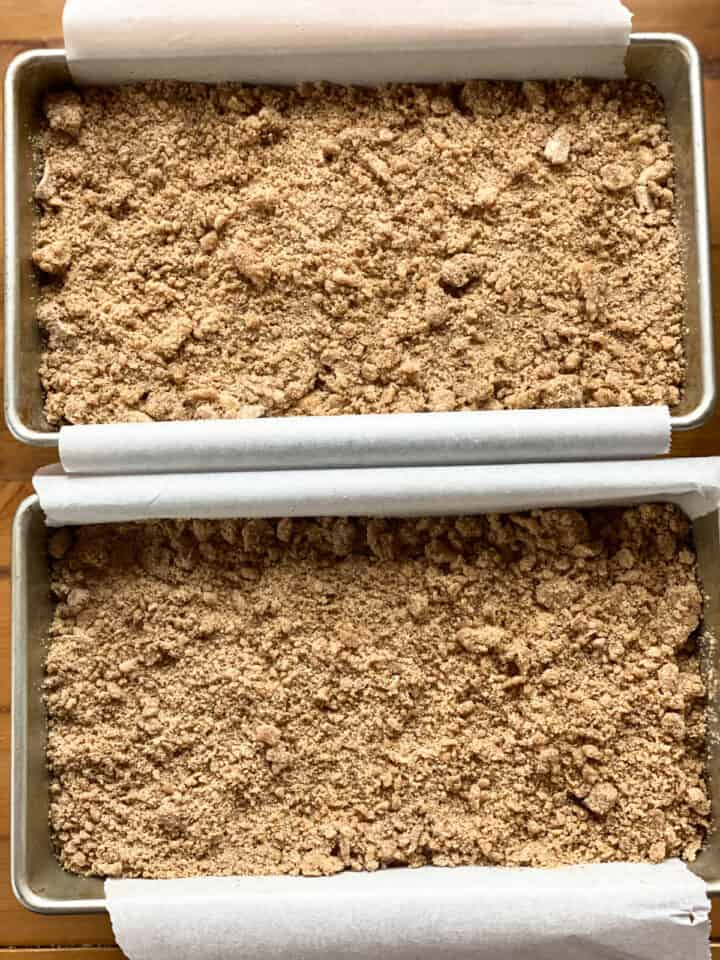 Crumb topping added on top of bread batter in rectangle loaf pans.