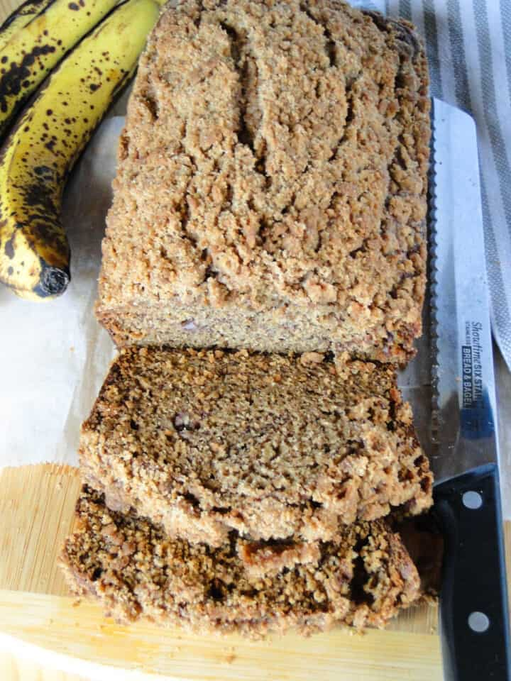 Top view of crumb topped banana bread with 2 slices on board.