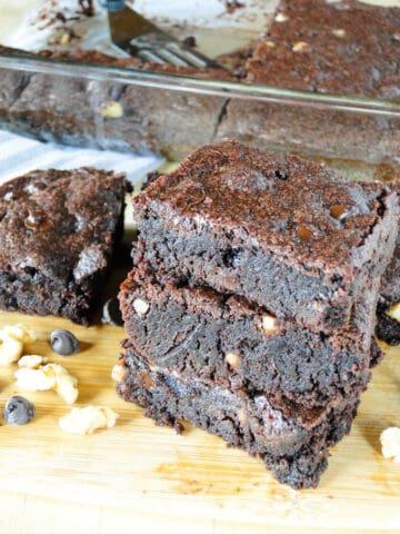 Dark chocolate walnut brownie slices stacked 3 high on board.