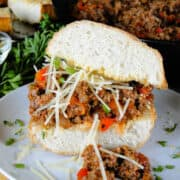 Side view of Italian sloppy joe on white round plate topped with shredded parmesan cheese.