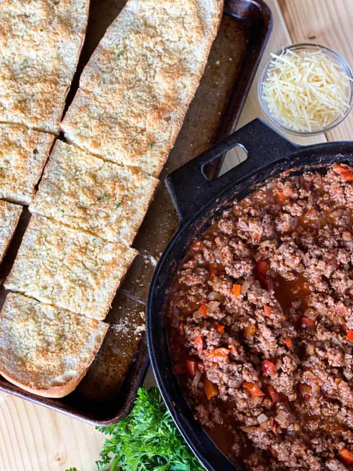Italian sloppy joes in cast iron pan next to sliced garlic bread on sheet pan.