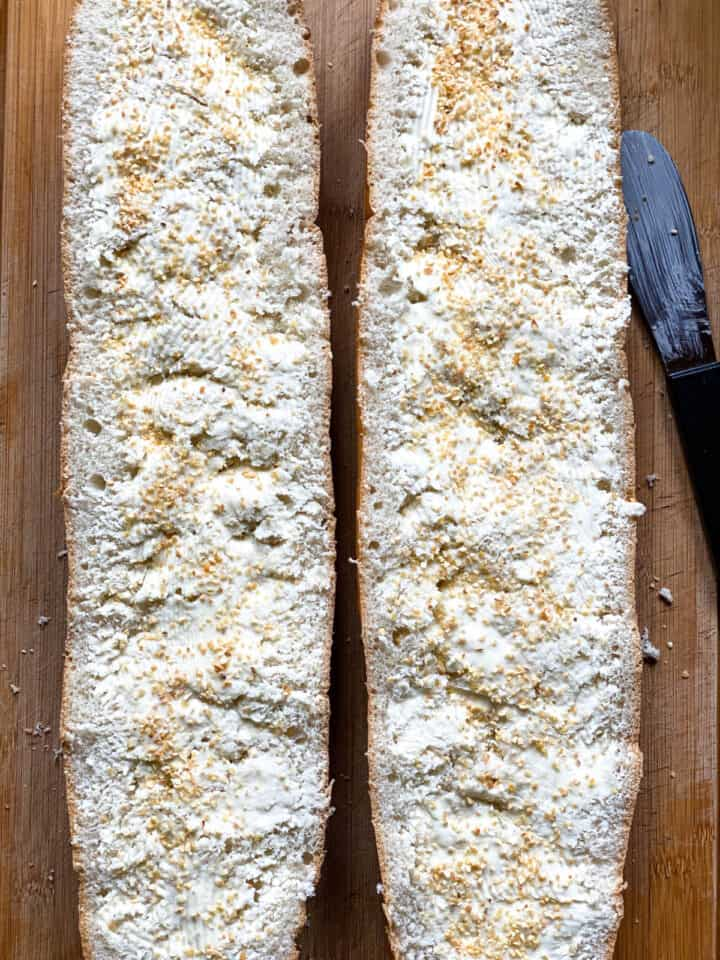Bread cut in half slathered with butter and sprinkled with minced garlic.