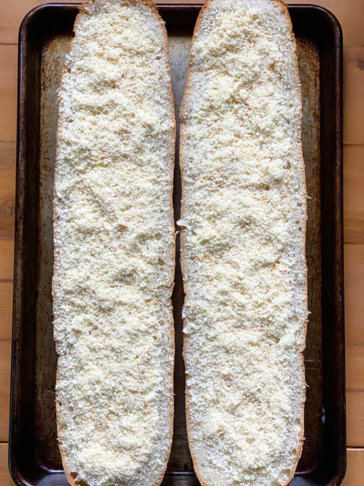 Garlic bread topped with grated parmesan cheese on sheet pan.