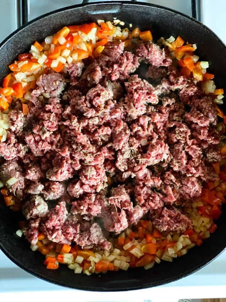 Sautéed veggies with ground beef in cast iron pan.