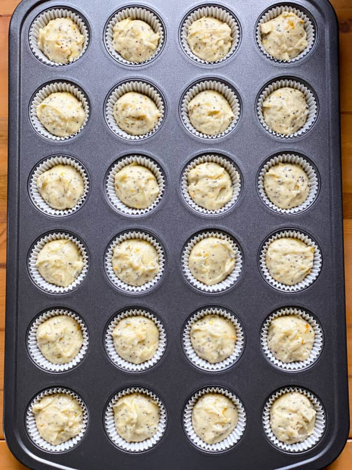 Mini muffin pan with paper liners filled with muffin batter.