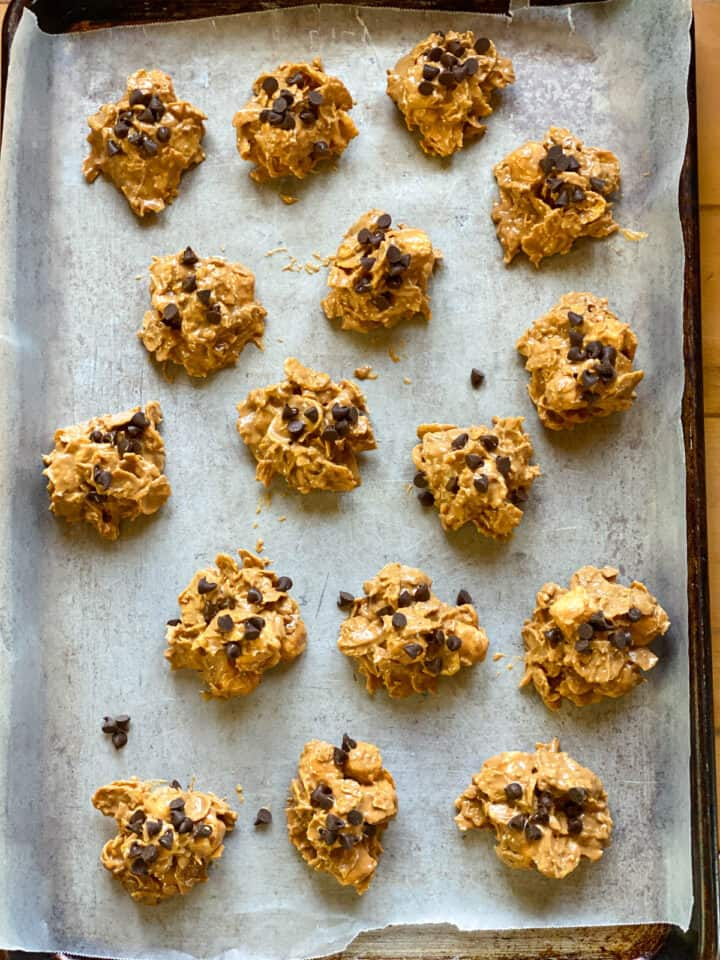 Cookies scooped on parchment lined sheet pan and topped with mini chocolate chips.