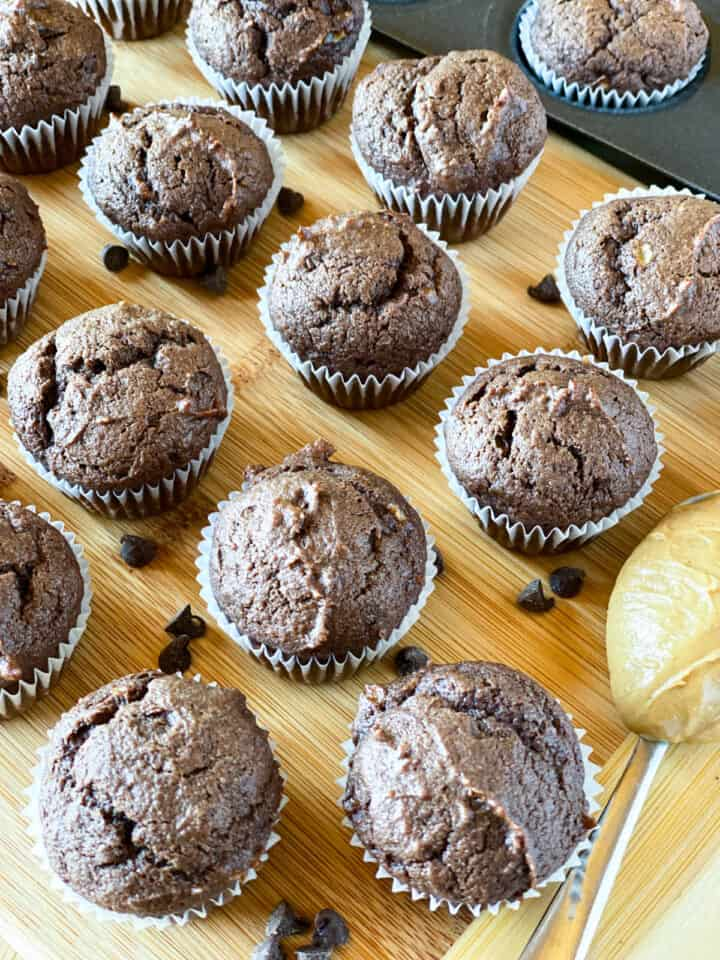 Top view of peanut butter banana chocolate muffins in rows on a board.