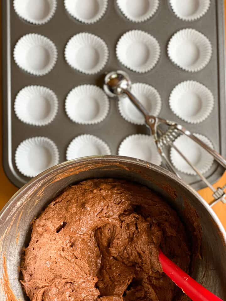 Completed muffin batter in bowl by mini muffin pan with paper liners and small scoop.