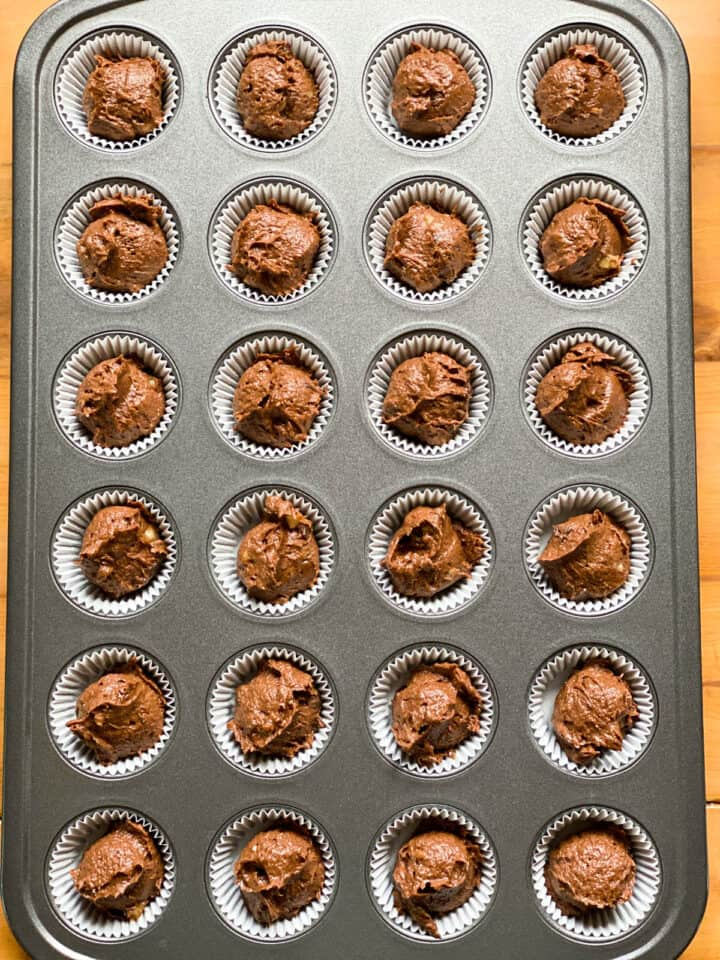 Muffin batter in paper liners in mini muffin pan.
