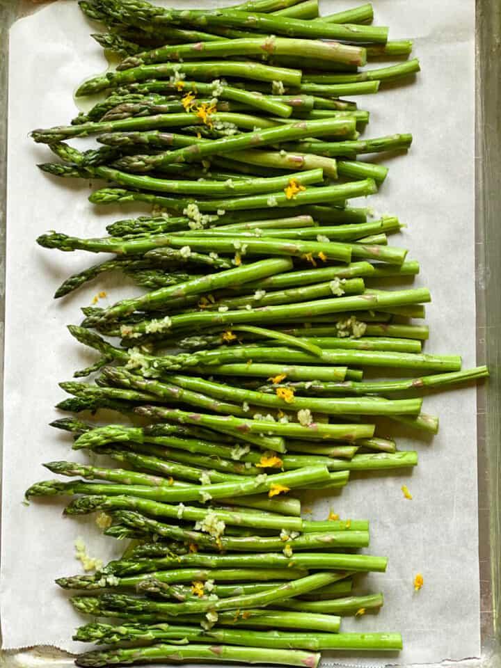 Trimmed asparagus on sheet pan with olive oil, lemon juice, garlic and lemon on top.