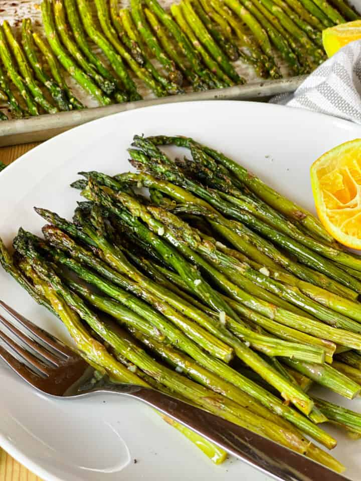 Roasted asparagus piled on white round plate with lemon half and fork.