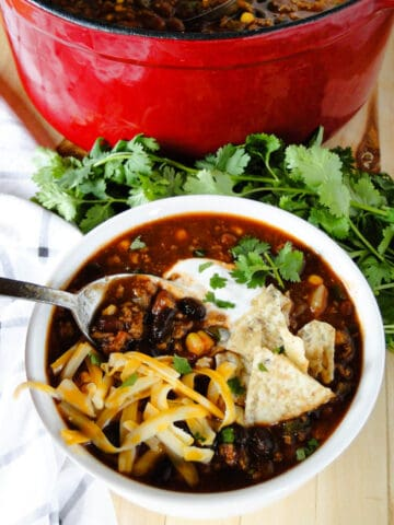 Ground turkey chili in bowl with spoon topped with sour cream, shredded cheese and crushed tortilla chips.