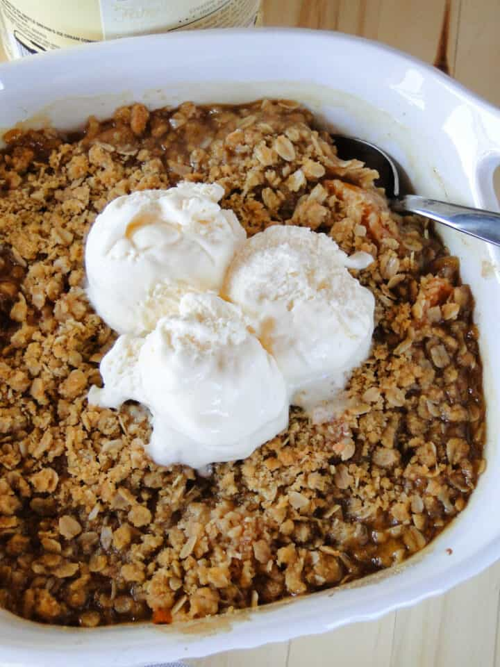 Easy peach crisp is white baking dish topped with 3 scoops of vanilla ice cream.