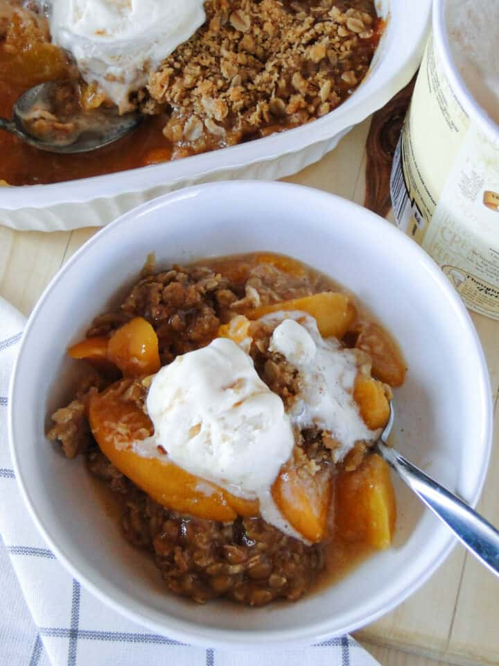 Top view of easy peach crisp in white round bowl with spoon in front of baking dish of peach crisp.