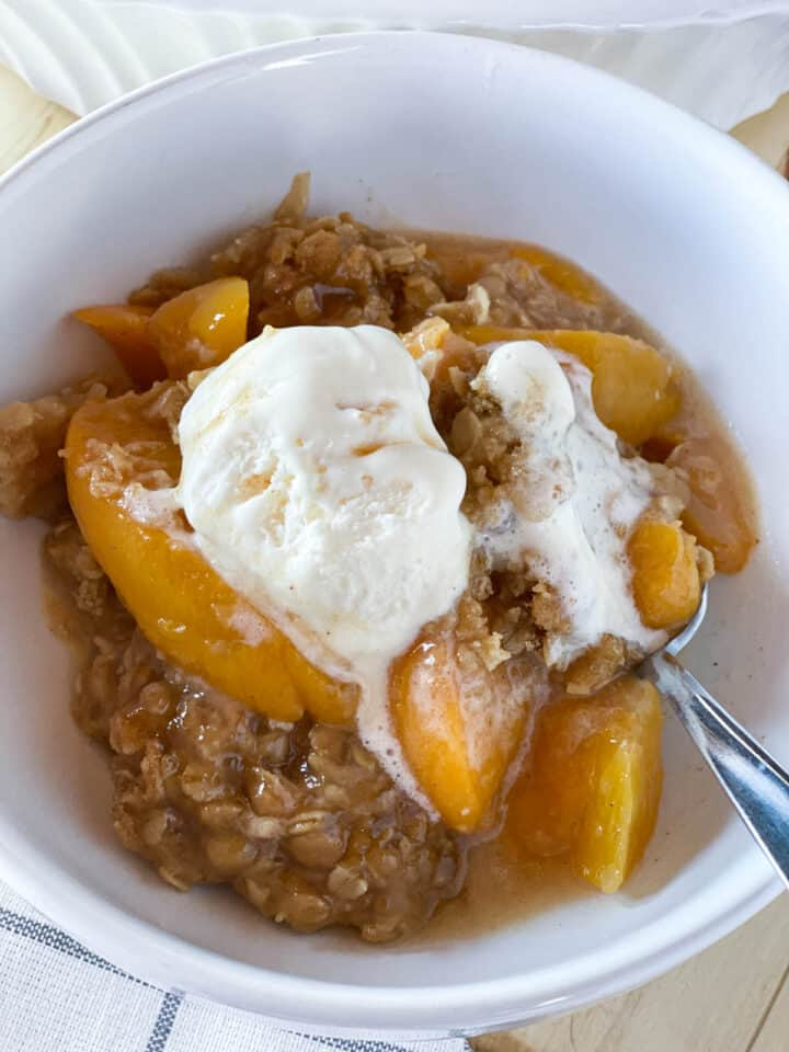 Close up view of easy peach crisp is white round bowl with spoon and topped with vanilla ice cream.