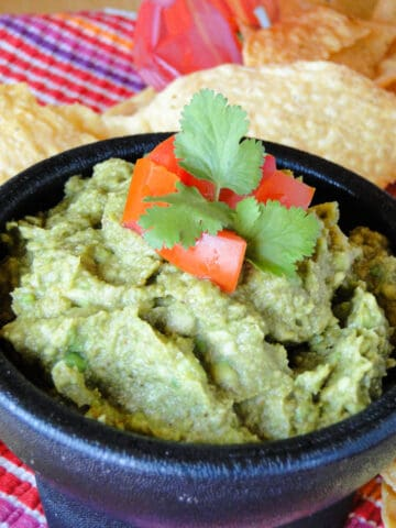 Easy homemade guacamole in bowl topped with diced tomatoes and cilantro leaves.