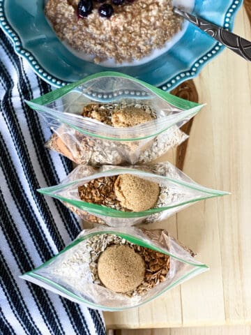Homemade instant oatmeal prepped in zip top bags sitting in front of a bowl full of cooked oatmeal.