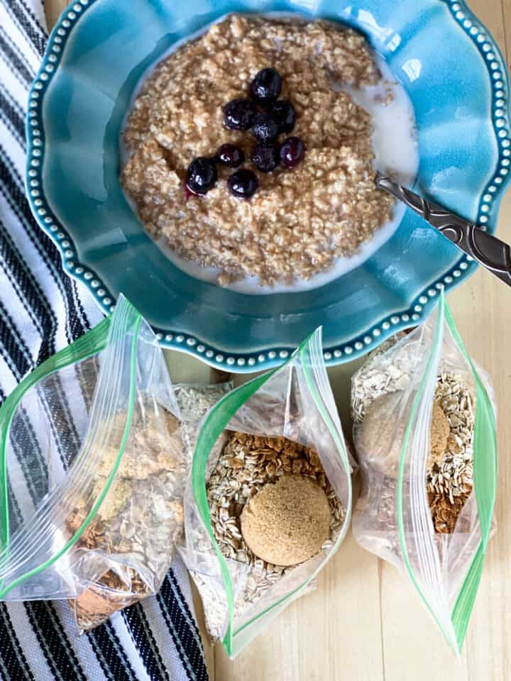 Homemade instant oatmeal packets prepared in front of a bowl full of cooked oatmeal topped with blueberries.