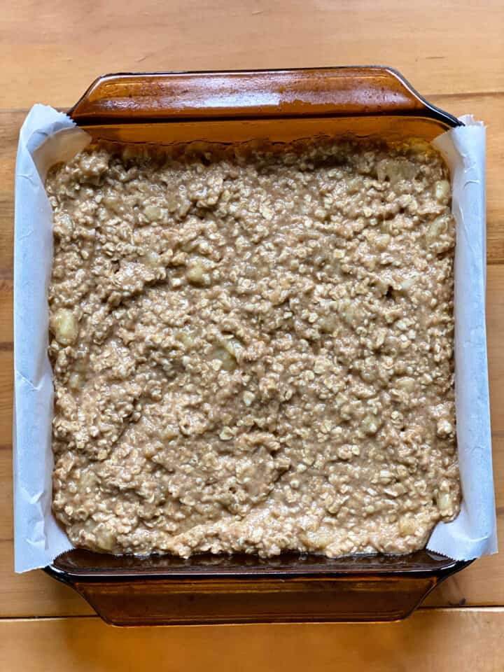 Bread spread into a lined 8x8 glass baking dish.