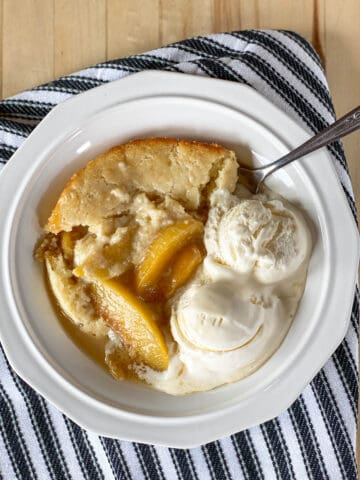 Top view of peach cobbler in white bowl with 2 scoops of vanilla ice cream and spoon.