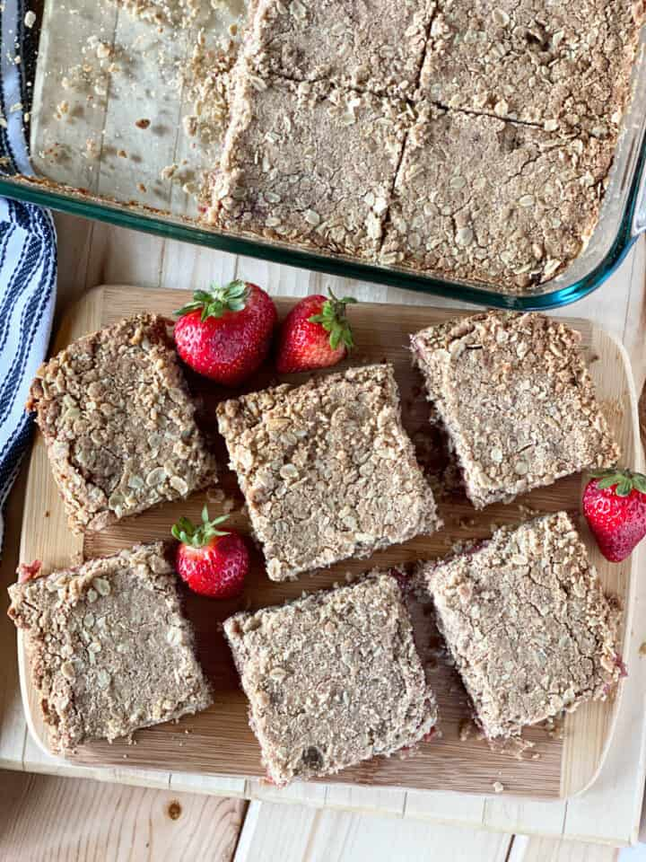 Top view of sliced strawberry rhubarb oat bars on board next to dish of bars.