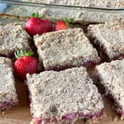 Strawberry rhubarb oat bars sliced into squares and on a board in front of the dish of bars.