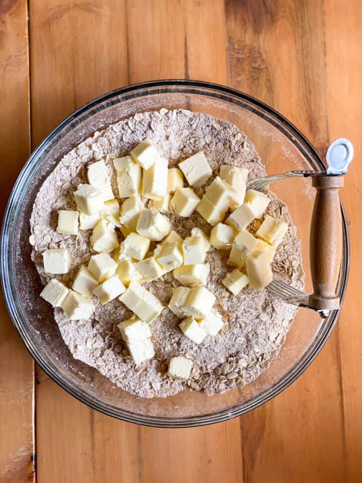 Cubed butter added to oatmeal crust dry ingredients.