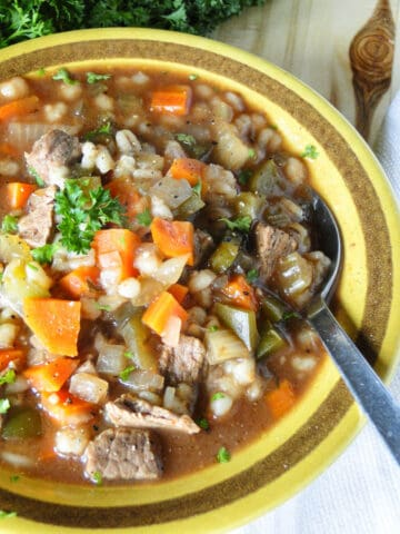 Close up view of crock pot beef barley stew in a round yellow bowl with spoon.