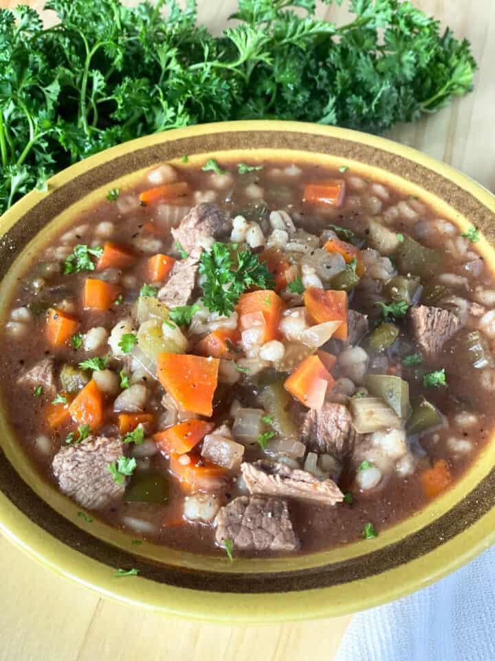 Crock pot beef barley stew in yellow bowl.