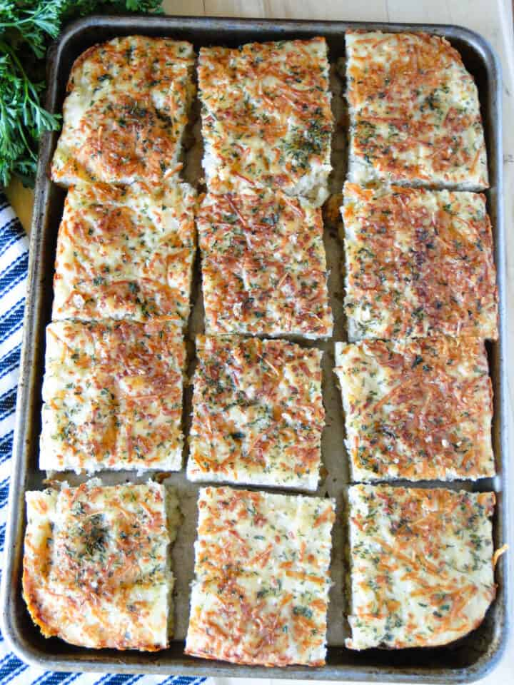 Baked garlic parmesan focaccia bread on sliced and on sheet pan.