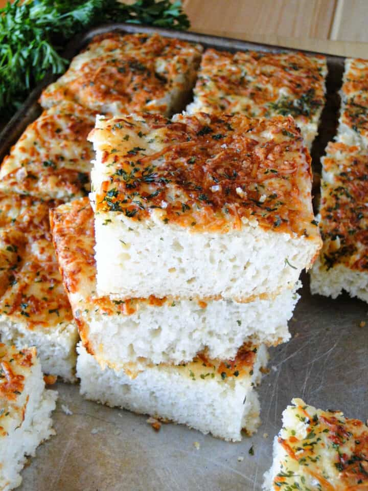 Sliced garlic parmesan focaccia bread stacked 3 high on sheet pan surrounded by more sliced bread.