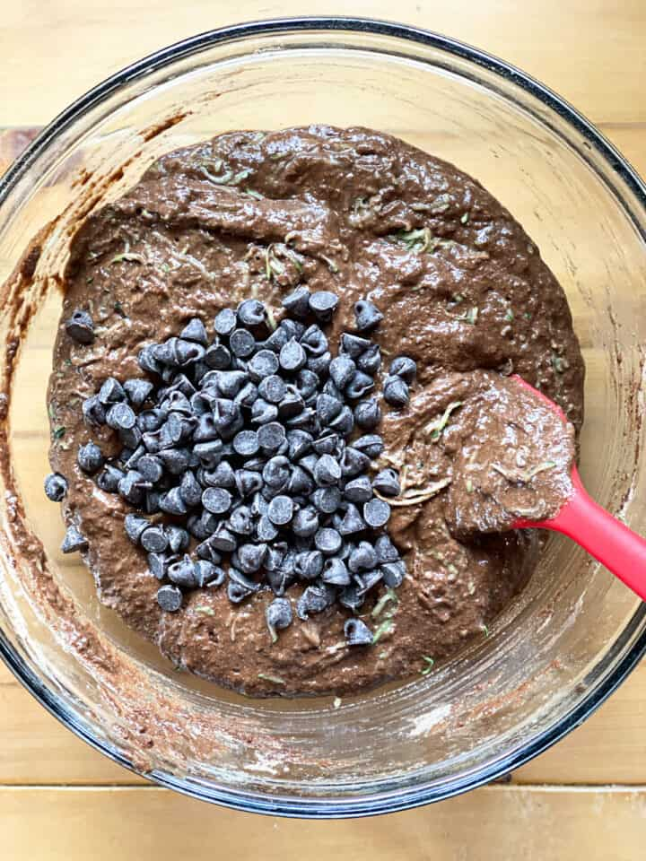 Chocolate chips added to muffin batter with zucchini.