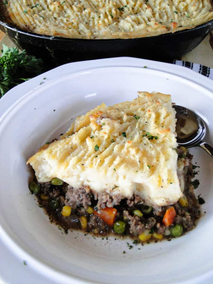 Homemade shepherd's pie served in a round white bowl with spoon in front of whole pan of pie.