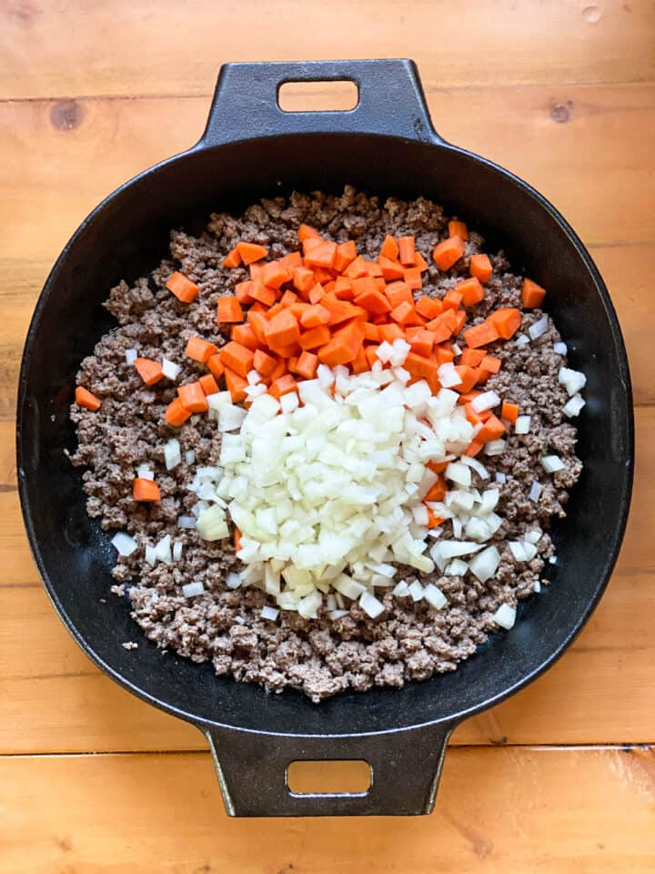 Ground beef cooked with onions and carrots added for shepherd's pie filling.