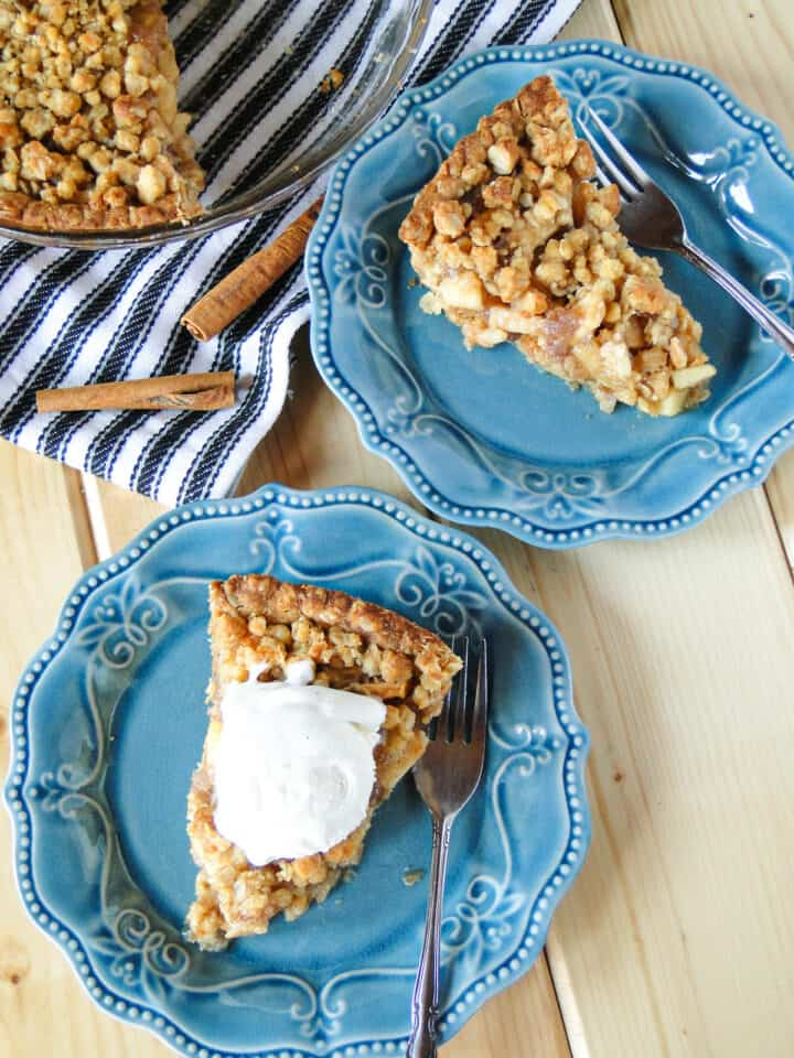 Two slices of apple crisp pie on blue round plates, one with a scoop of ice cream on top.