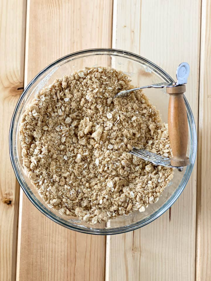 Streusel oat topping mixed together in large glass bowl with pastry blender.