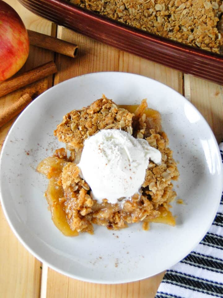 Top view of serving of apple crisp on white round plate with scoop of vanilla ice cream on top.
