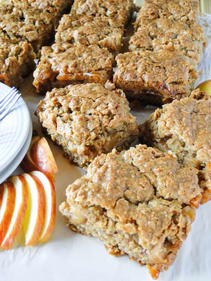Apple pie bars squares on parchment paper with garnish of apple slices.