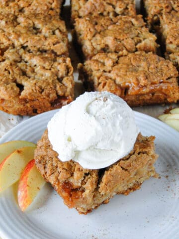 Apple pie bar with scoop of vanilla ice cream on white round plate in front of sliced bars.