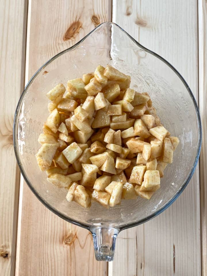 Apple pie filling mixed together in glass bowl.