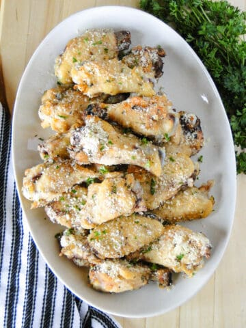 Top view of crock pot garlic parmesan chicken wings on white oval platter.