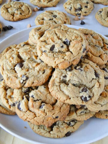 White round plate full of chocolate chip butterscotch peanut butter cookies.