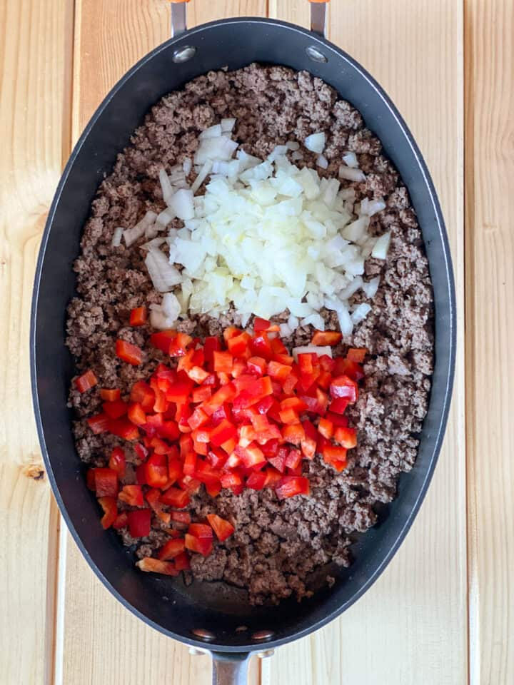 Chopped onions and bell pepper added to cooked ground beef in skillet.