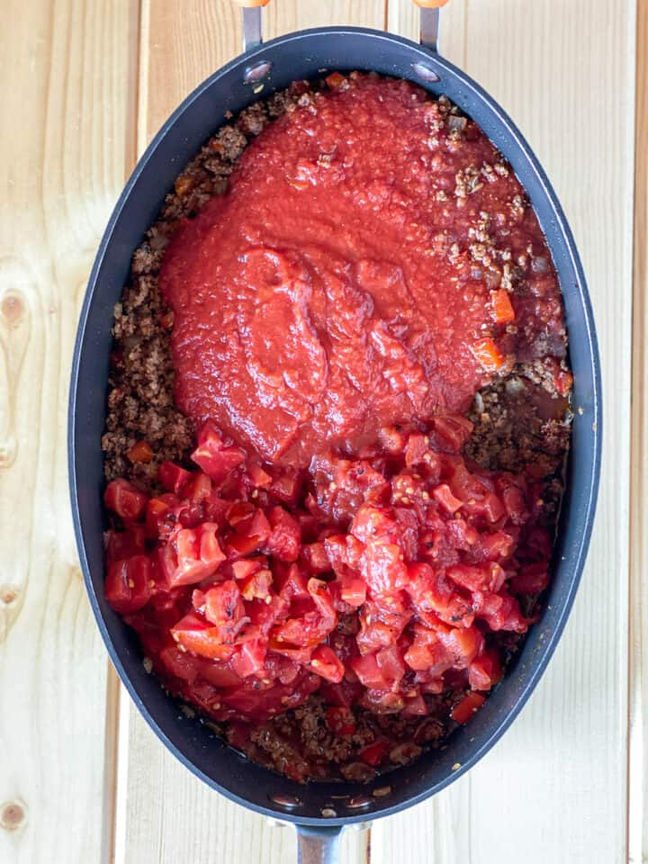 Crushed tomatoes and diced tomatoes added to skillet with cooked ground beef mixture.