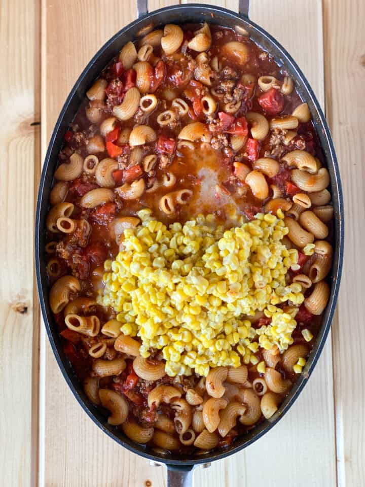 Frozen corn added to the cooked macaroni, tomato and beef mixture in large skillet.