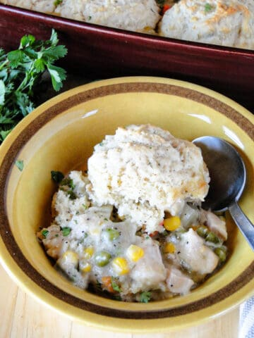 Bowlful of easy chicken pot pie with biscuits and spoon.