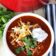 Top view of easy chicken taco soup topped with shredded cheese, sour cream and cilantro.
